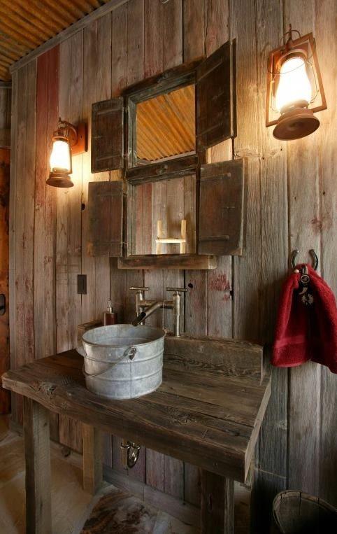 un bagno rustico incontra il vintage con molto legno macchiato e un lavandino fatto di un secchio di metallo