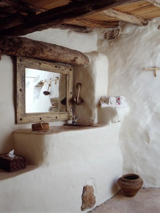un bagno rustico e wabi-sabi con pareti bianche e molto legno e legni galleggianti