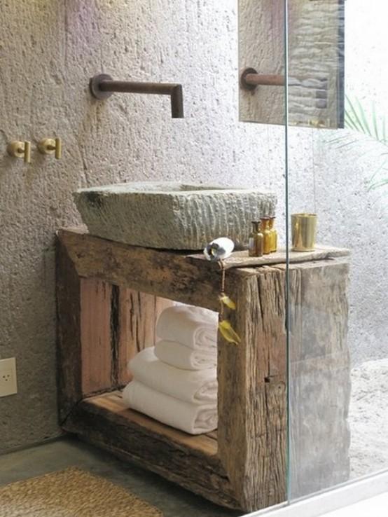 un bagno wabi-sabi con un lavabo in legno stagionato e molta pietra tutt'intorno