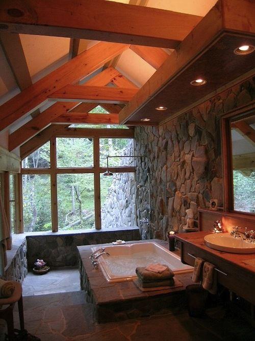 un bagno di chalet mansardato fatto con molta pietra naturale e legno e con due pareti vetrate