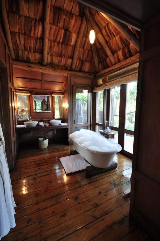 un bagno rustico con una parete vetrata, una vasca da bagno e lucernari per godere della luce naturale