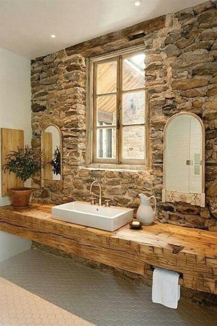 un muro in pietra naturale, un lavabo in legno e un pavimento in piastrelle per un accogliente spazio rustico dai colori chiari