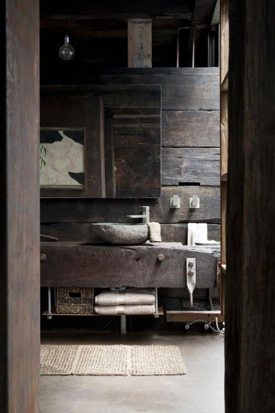 un bagno wabi-sabi con pareti in legno stagionato e un lavandino in pietra più un pavimento di cemento
