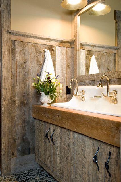 un bagno rustico con molto legno stagionato e una grande vanità