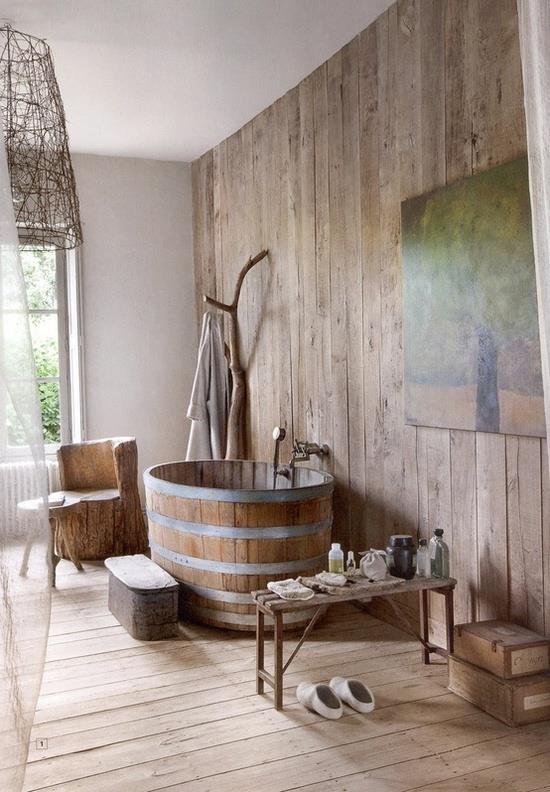 un bagno rustico accogliente e arioso con molto legno, una vasca in legno e un baule per stendere i vestiti