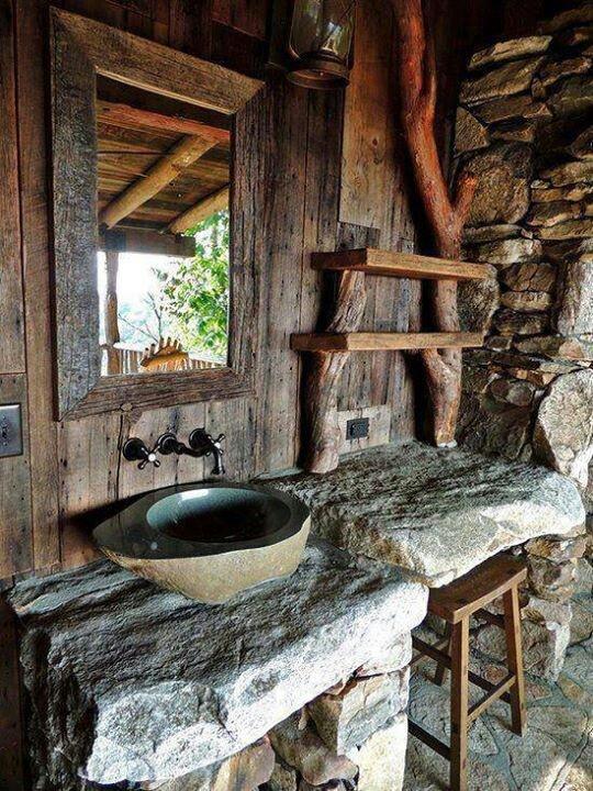 un bagno wabi-sabi con legno, pietra e cemento più un grande specchio e un lavabo in pietra