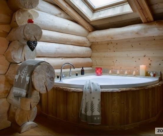 un bagno rustico con molto legno chiaro e una vasca rivestita in legno più un lucernario
