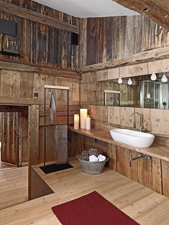 un bagno rustico incontra vintage con candele e lampade più una vasca con asciugamani