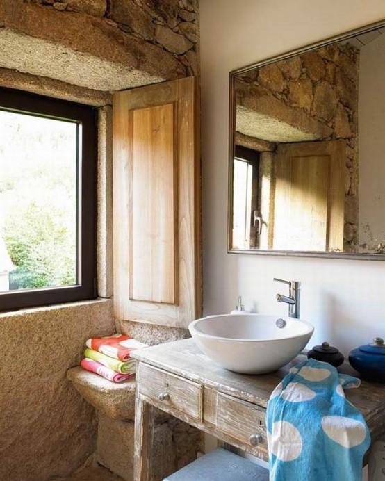 muri in pietra, persiane in legno e un lavabo in legno per un look rustico incontra vintage