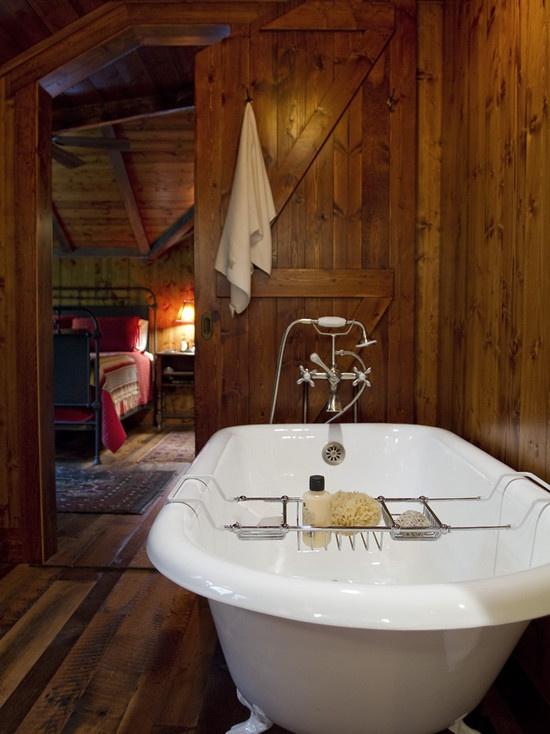 un bagno rustico tutto rivestito di legno tinto e una vasca da bagno vintage