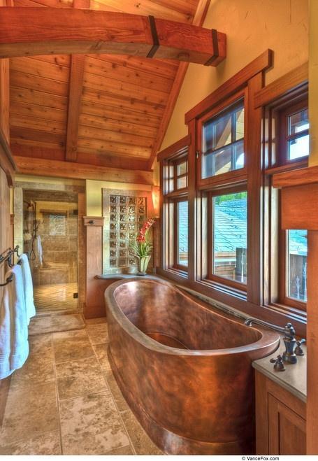 un bagno rustico con soffitto in legno e trave, finestra con intelaiatura in legno, pavimento piastrellato e vasca in metallo