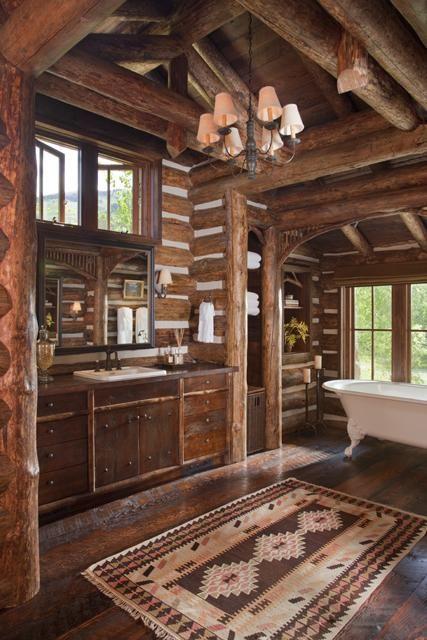 un bagno rustico con molta sequoia e un lampadario più alcuni tappeti boho chic