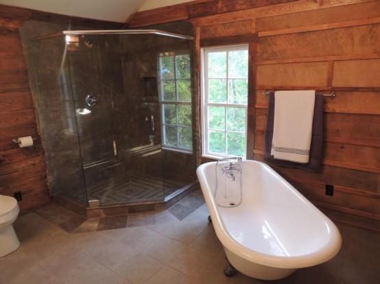 un bagno rustico con pareti in legno e pavimento in piastrelle più uno spazio doccia rivestito in vetro