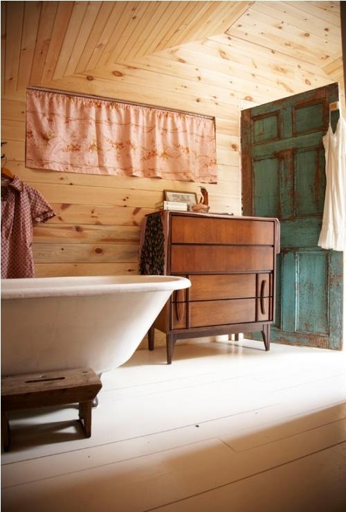 un bagno rustico incontra il vintage con un pavimento in legno imbiancato e pareti tinteggiate di luce più una credenza e una porta