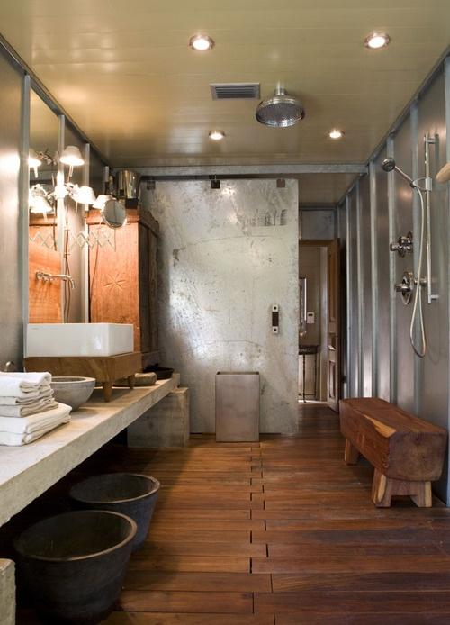 un bagno industriale con molto legno, metallo e cemento e lampade dappertutto