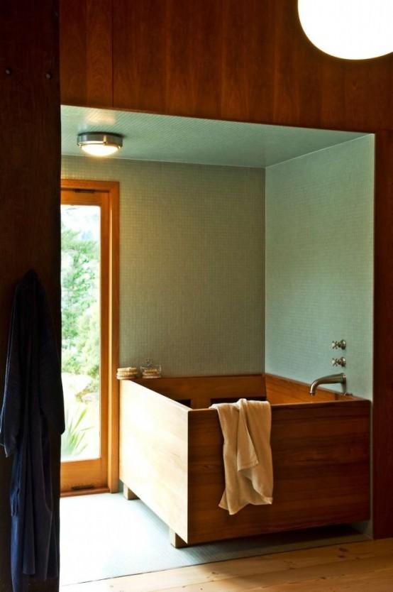 un bagno moderno con piastrelle verdi e una vasca quadrata in legno