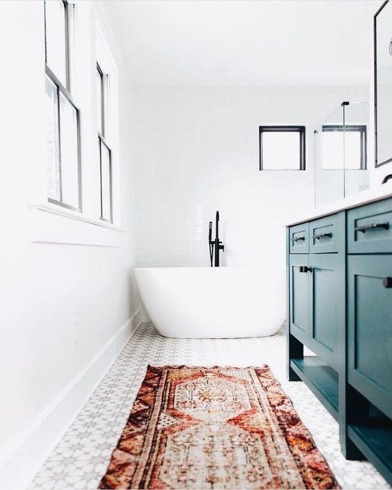 un luminoso bagno eclettico fatto in bianco e neutri e accentuato con un tappeto boho rosso e una vanità verde acqua
