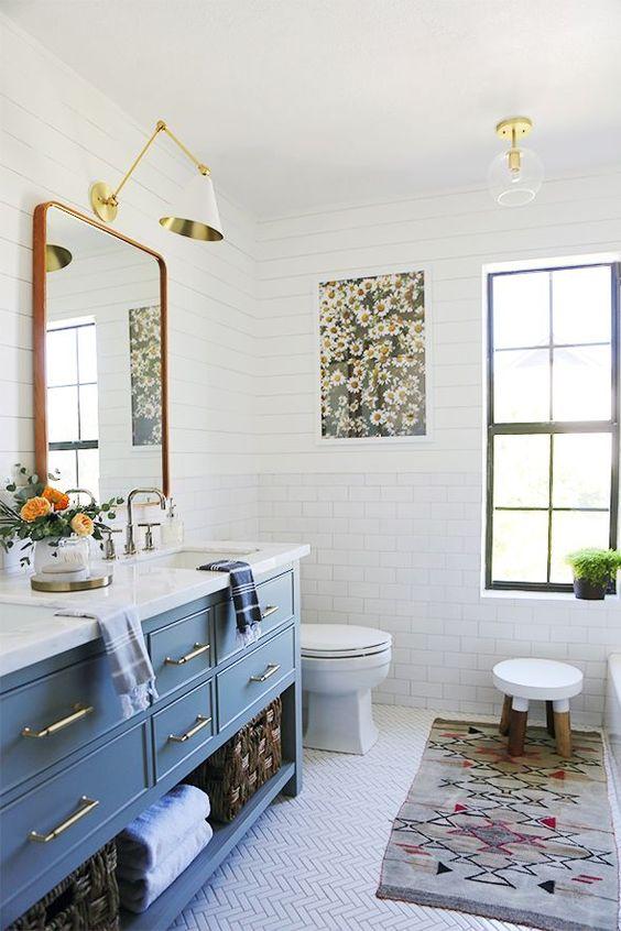 un colorato bagno eclettico con una vanità blu, un tappeto colorato e un'opera d'arte floreale