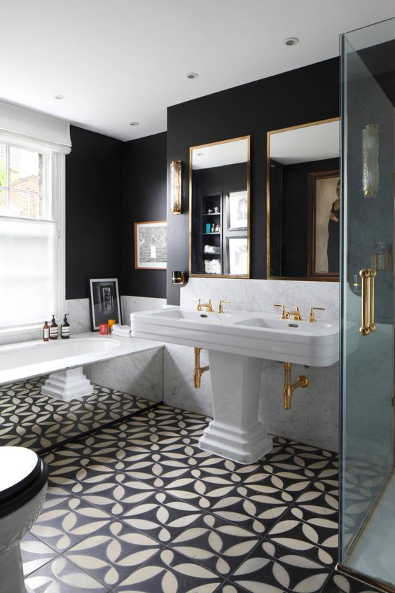 uno splendido art déco incontra un bagno vintage in bianco e nero, con una vasca rivestita di specchi e un grande doppio lavabo