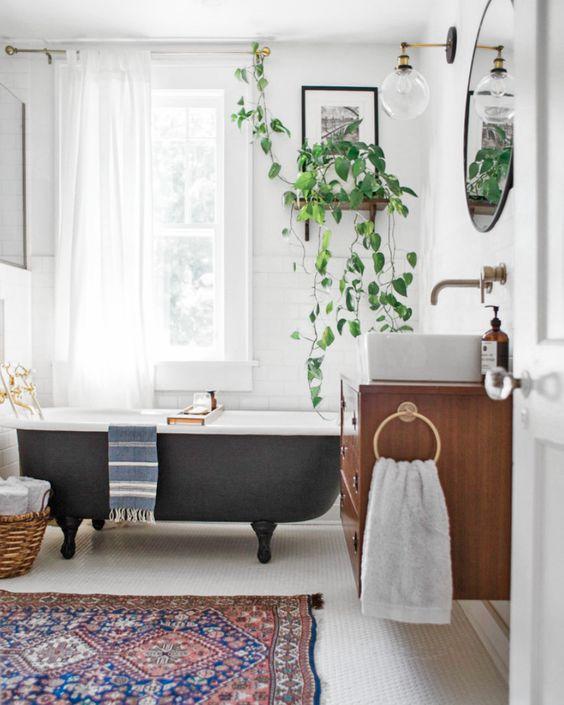un bagno eclettico vintage con un tappeto boho, una vasca da bagno nera vintage, piante in vaso e un mobile da toeletta con lavandino