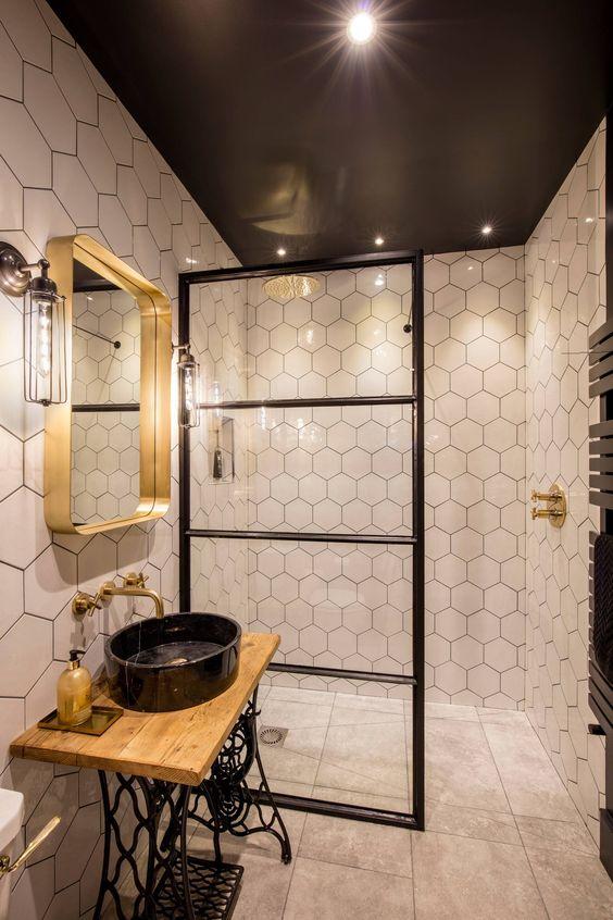 uno splendido bagno eclettico che mescola bagno industriale e contemporaneo e realizzato in una combinazione di colori nero, bianco e oro