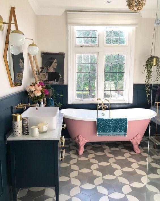 una splendida vasca da bagno con piedini a rullo rosa e piastrelle sul pavimento, il tutto unito a un arredamento blu scuro e un'illuminazione d'effetto