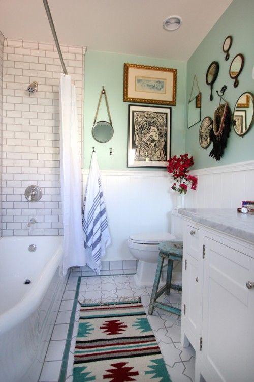 un bagno vintage incontra boho chic, con molti specchi e dipinti, con un tappeto colorato e piastrelle della metropolitana