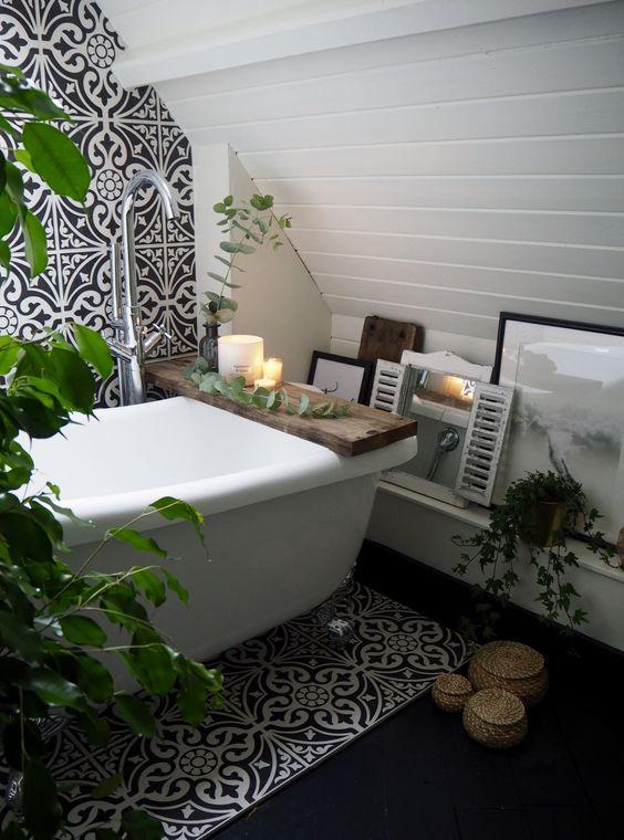 un bagno eclettico con piastrelle art déco bianche e nere, con tocchi boho come contenitori di vimini e vegetazione e decorazioni in vaso