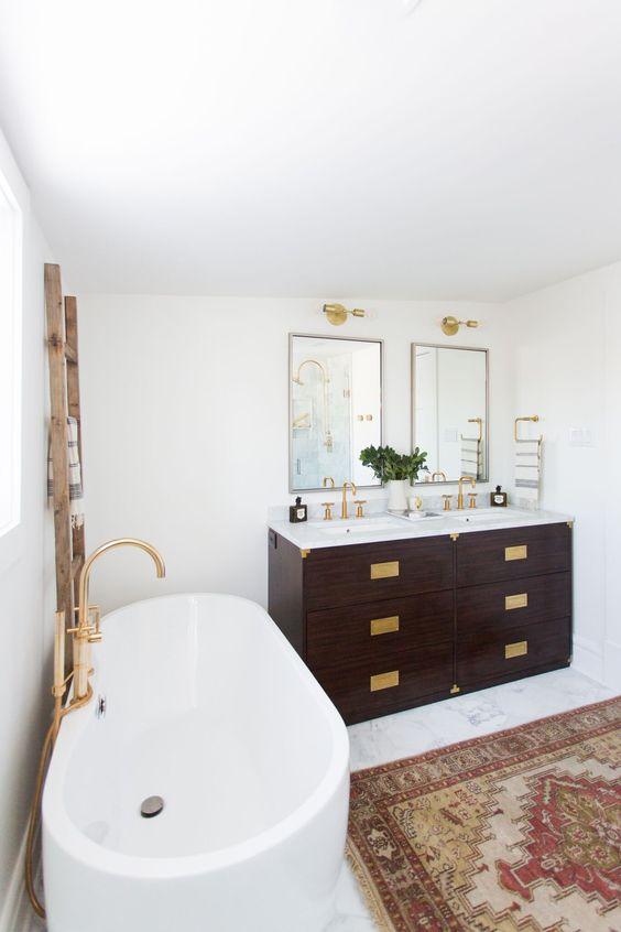 un art déco incontra un bagno eclettico boho con un sacco di ottone, tappeti boho e vanità macchiate scure
