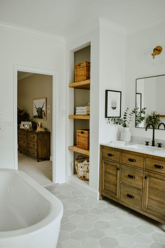 un boho eclettico incontra un bagno moderno della metà del secolo con una vanità in legno, cestini, piastrelle esagonali e vegetazione in vaso