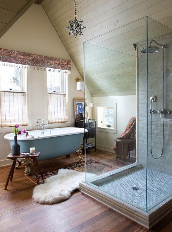 un opulento bagno eclettico con tocchi di blu polvere, una doccia piastrellata, tappeti boho e una tenda stampata boho