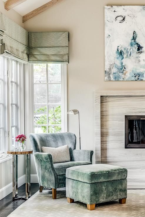 un angolo lettura riempito con una sedia a spina di pesce di velluto blu e un pouf abbinato, un tavolino piccolo e carino