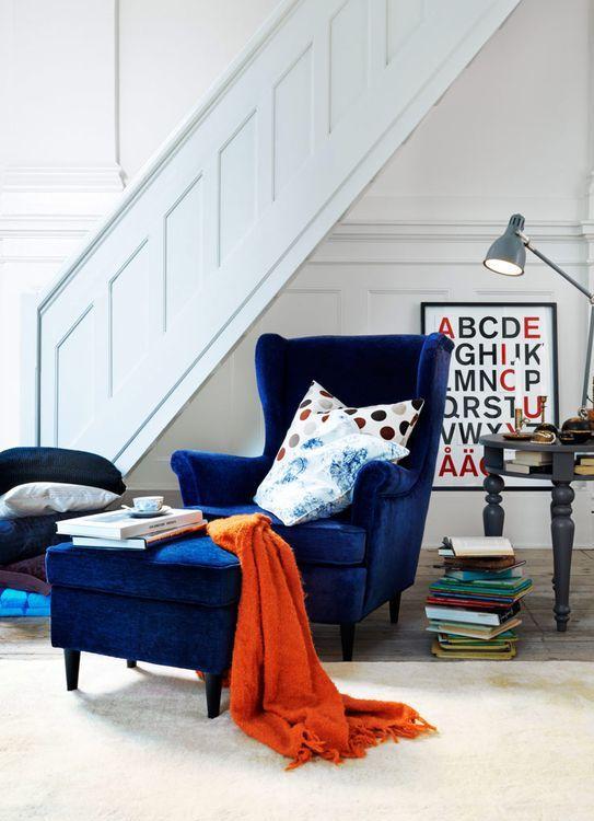 una sedia wingback in velluto blu scuro con un ottomano coordinato e alcuni cuscini colorati per una lettura confortevole