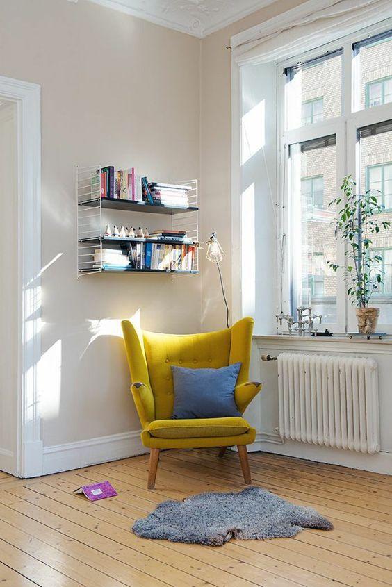 una sedia a schienale alto senape con un cuscino blu e un tappeto grigio vicino alla finestra è un'idea carina