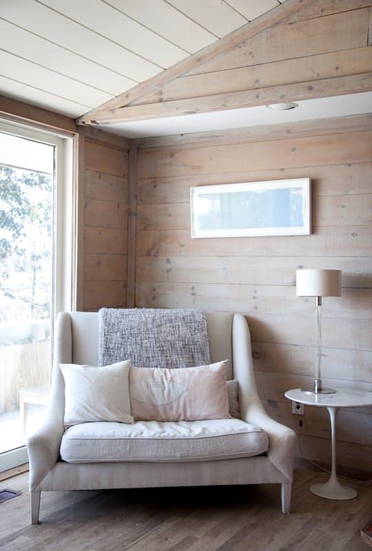 una comoda sedia neutra di grandi dimensioni con cuscini e cuscini posizionati vicino alla finestra per leggere comodamente