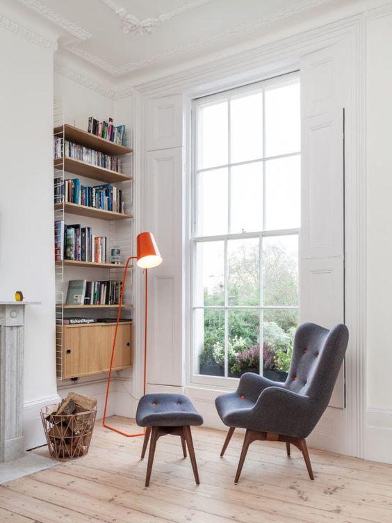 una sedia con schienale alare grigio di ispirazione retrò con poggiapiedi abbinato e tocchi di arancione più una lampada arancione audace