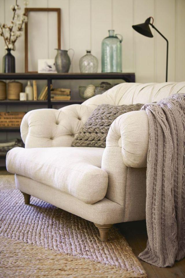 una splendida e grande sedia imbottita color crema, con gambe in legno e una coperta in maglia e un cuscino in cui affondare