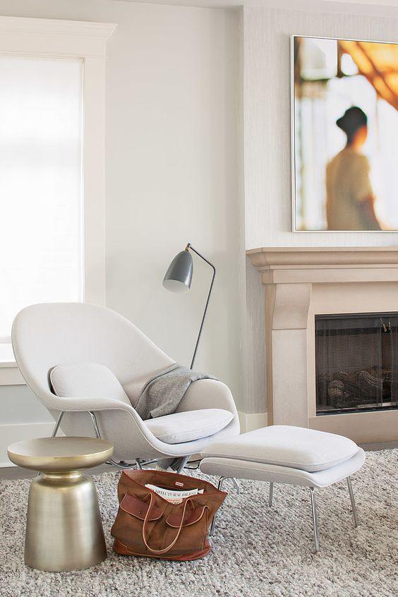 una comoda sedia bianca ispirata alla metà del secolo e un poggiapiedi abbinato, una lampada da terra in metallo e un tavolino in metallo per un angolo confortevole