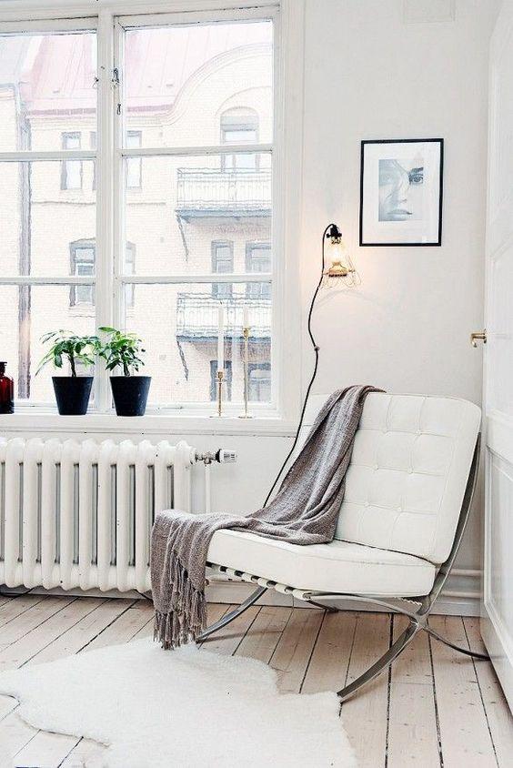 una comoda sedia contemporanea in metallo e pelle bianca e una coperta per una lettura accogliente