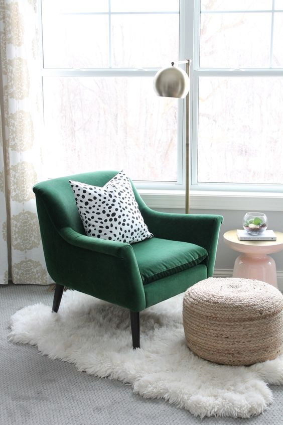 una sedia di velluto verde con un cuscino a pois, un ottomano intrecciato, un tappeto di pelliccia e una lampada da terra in metallo