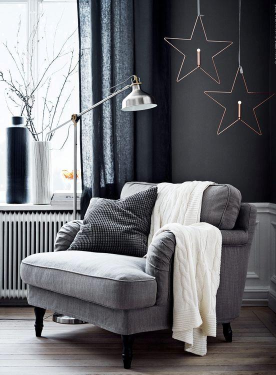 una semplice sedia imbottita grigia vicino alla finestra, una lampada da terra in metallo, cuscini e una coperta lavorata a maglia