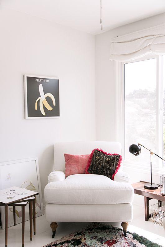 una sedia bianca imbottita con cuscini vicino alla finestra è un bel pezzo di arredamento su cui leggere