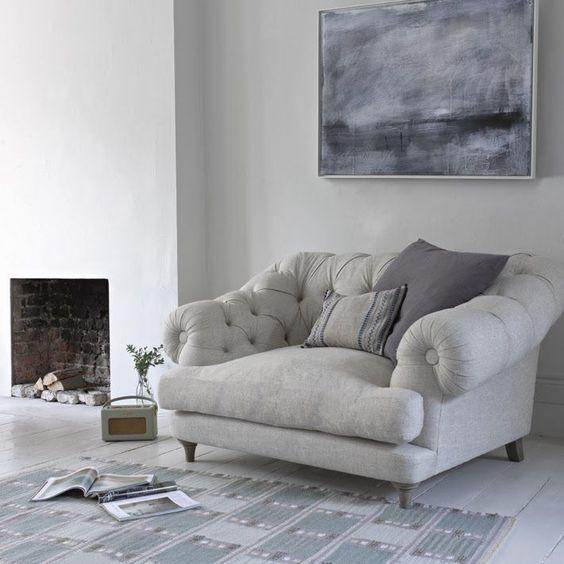 una sedia grigia imbottita e cuscini accanto al caminetto è uno dei posti più comodi in cui leggere