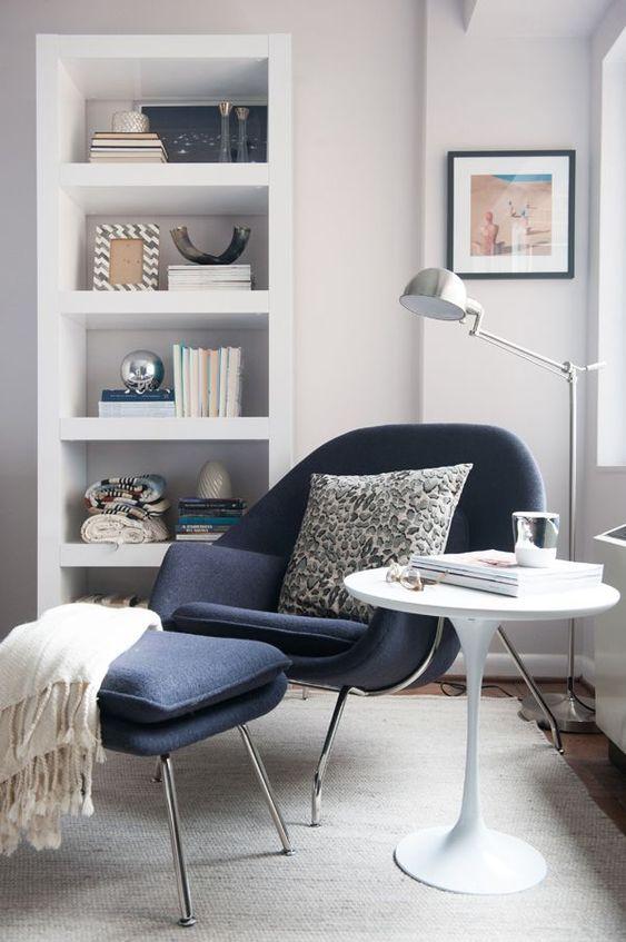 una sedia blu scuro e un poggiapiedi su gambe metalliche alte ispirate ai design moderni della metà del secolo