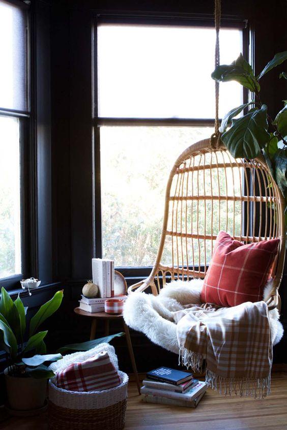 una sedia a gabbia in rattan sospesa con cuscini, una coperta, un copriletto di pelliccia è una splendida base per un angolo di lettura