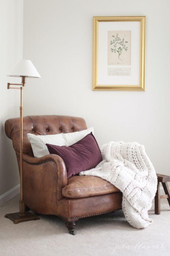 una sedia in pelle marrone di ispirazione vintage con cuscini e una coperta in maglia è sempre una buona diea da provare