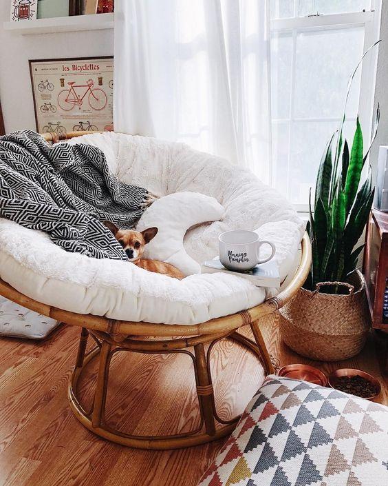 una sedia rotonda in rattan con cuscini e cuscini più un copriletto di pelliccia è estremamente accogliente per godersi la lettura vicino alla finestra