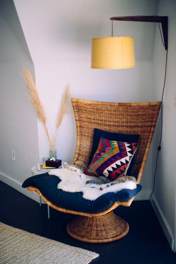 una sedia intrecciata su un supporto con cuscini, thrwos e coperte è un'idea elegante per uno spazio boho