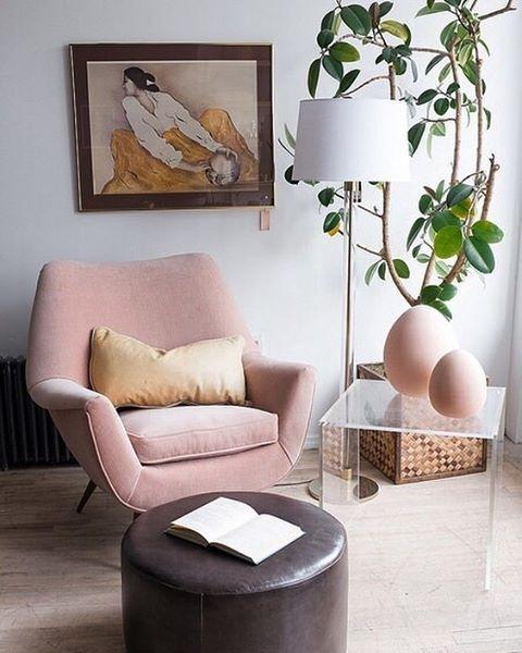 una sedia moderna di metà secolo arrossata con curve e angoli è un pezzo interessante, e un ottomano marrone lo contrasta