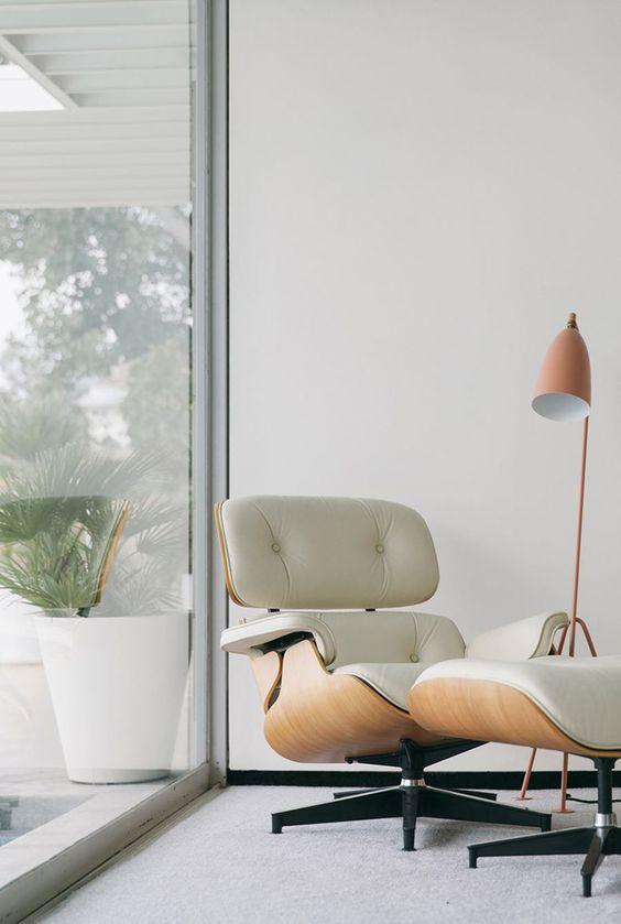 Poltrona lounge Eames in compensato e pelle bianca e poggiapiedi abbinato vicino alla finestra